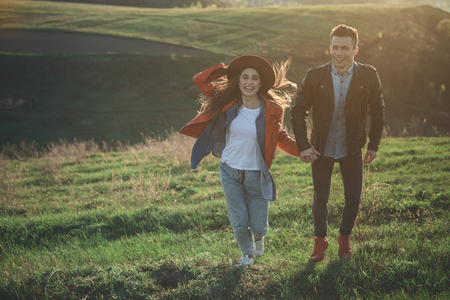 Full length of happy young people holding hands and flipping on meadow in summer evening. Girl is holding hat. Copy space in left side Stock Photo