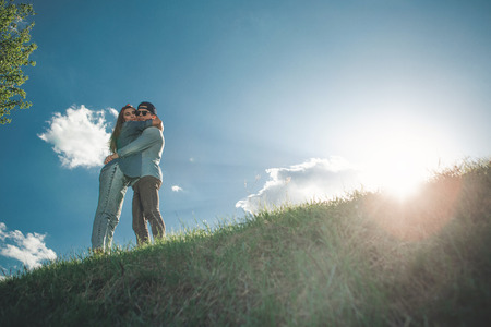 You are my everything. Low angle full length of attractive young people surrounded by colourful summer landscape and holding each other tightly. They are happy and calm. Copy space in right side