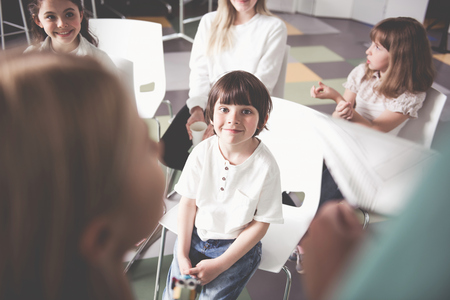 Portrait of happy boy sitting on chair near glad comrades during interesting lesson. Positive children telling