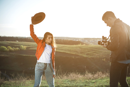 Full length of focused man with camera in hands. He is taking pictures of girlfriend in summer evening. Female is posing with funny face raising hat