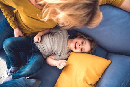 Top view of laughing son spending great time and looking at camera with joy. He is lying on sofa near his mother who is tenderly watching him. Parent is entertaining kid by kindly fondling