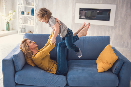 Happy family are rejoicing and playing in living-room. Mom is lifting son on her legs while lying on sofa. They are gently holding hands and looking at each-other