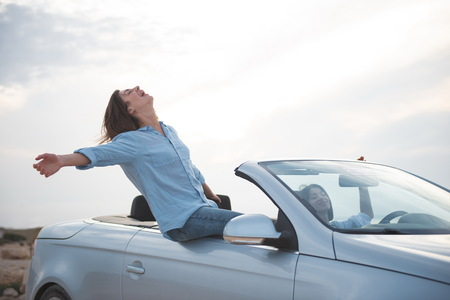 Full of admiration. Happy girl is sitting on fashionable cabriolet with her hands outstretched while expressing rapture. She is travelling by car along seashore with her friend female. Summer concept Stock Photo - 103042576