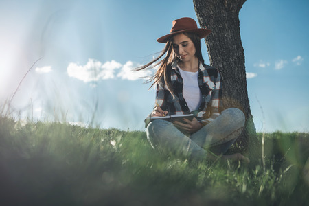Dear diary. Full length of young woman concentrated on writing in copybook nearby tree on green meadow. She is calm and smiling enjoying nice warm summer weather. Copy space in left side