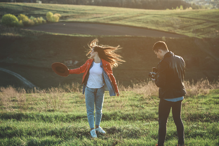 Full length of charming girl having photo session among amazing landscape with boyfriend. Boy is concentrated and photographing woman with in motion Stock Photo