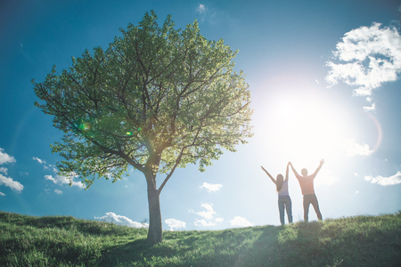 Summer happiness. Full length of young couple raising their hands to bright sun. They are standing by tree with joy and excitement Stockfoto