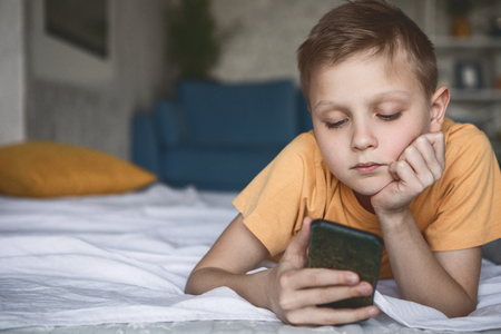 Portrait of pensive little child looking at modern mobile while lying on cozy bed in room. Wistful boy using gadget concept Banco de Imagens