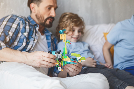 Thoughtful male telling with happy child while keeping toy in arm. Entertainment at home concept Stock Photo