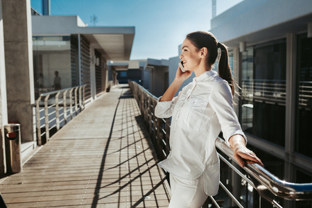 Side view profile of happy lady in white clothes holding cellphone near her ear and communicating. She is standing on balcony. Copy space in left side Stockfoto