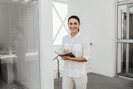 Portrait of female employee standing in office and holding opened notepad. She is looking at camera. Copy space in left side