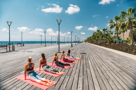 Flexible young women are practicing yoga on the wooden seafront. They are looking at water with enjoyment while doing exercise in the summer. Group lessons concept