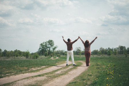 We are free. Joyful loving couple is standing on grassland path with relaxation. They are holding and stretching hands up with excitement. Focus on their back