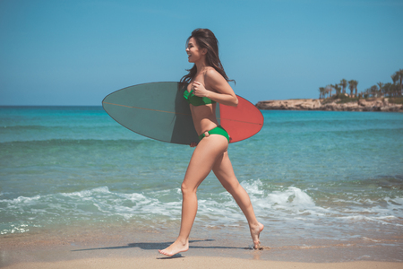 Excited young woman is running along the beach with surfboard. She is looking at the sea and laughing