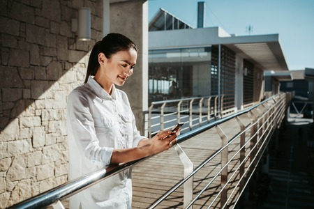 Satisfied woman enjoying summer weather on balcony. She is staring at her cellphone. Copy space in right side Stock Photo