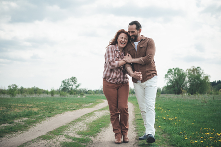 Full length portrait of happy man and woman hugging while walking on meadow path. They are laughing