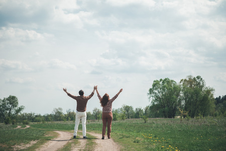 This is the real freedom. Carefree man and woman raising arms up to the sky. They are standing on meadow path