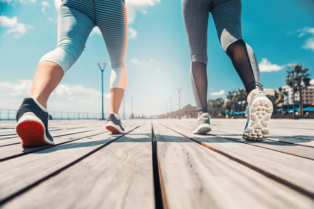 Low angle close up of female feet running along the wooden path. Two girls are training near the sea