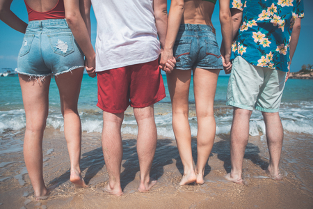 Close up of male and female back. Four friends are standing on the beach in front of the sea and holding hands. Friendship concept  Stock Photo
