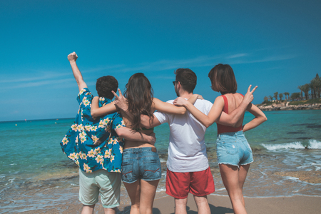 Cheerful young guys and girls are looking at the water with enjoyment. They are standing and embracing while turning back. Funny company entertainment at seaside concept  Stock Photo