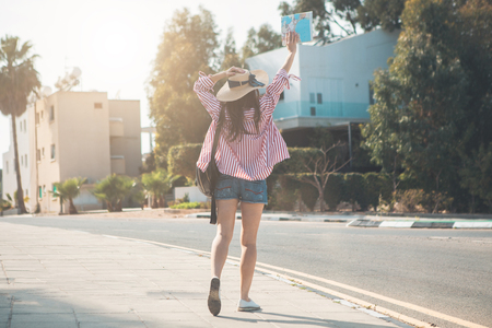 Cheerful female tourist is strolling on street while raising map up in hand. Focus on her back. Summer vacation concept