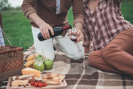 Close up of man arm pouring red wine from bottle into glass. Woman is sitting near husband on the blanket and relaxing. Romantic picnic on grass field concept