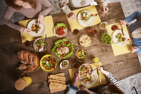 Top view of variety of dishes served for four people. They are eating salads, vegetables, meat, bread, rice and communicating