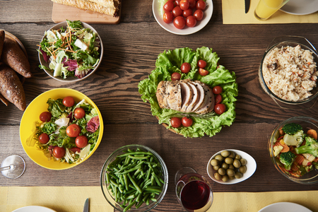 Top view of nutritious food cooked for tasty dinner. There are roast decorated with lettuce, veggie salads, bread, red cherry tomatoes and rice with spices Stock Photo