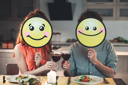 We are happy together. Portrait of joyful couple clinking glasses of red wine. Man and woman are holding positive smiles near their faces while sitting at table in kitchen