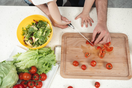 Top view close up of male hands cutting tomato together with child on wooden board. Father and daughter cooking healthy breakfast concept  Stock Photo