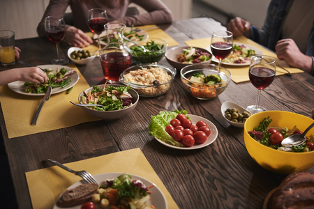 Close up of healthy dishes lying on wooden board. Family sitting together and eating vegetables, salads, rice, tomatoes, and drinking red wine