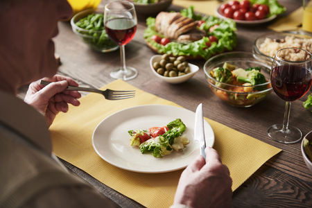 Close up of senior male sitting at board full of healthy meal with knife and fork in hands. He is having salad while socializing Stock Photo
