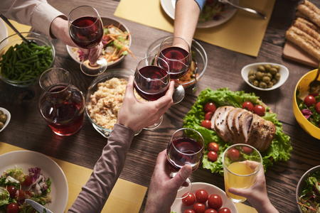 Top view close up of wine glasses holding by family at table. They are clinking goblets while eating home cooked dishes with vegetables and healthy ingredients Stock Photo