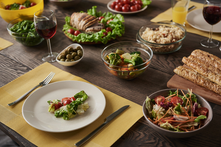 Close up of delicious healthy meal. White plate with salad lying together with vegetables, meat, and other nutritious dishes in different bowls on brown wooden board Stock Photo