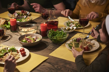 Close up festive dinner decorated with candles. Family is eating vegetables, asparagus, rice and drinking wine in pleasant atmosphere Stock Photo