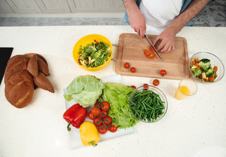 Healthy lifestyle. Top view close up of male arms chopping tomatoes into pieces. Abundance of fresh vegetables and bread are on table