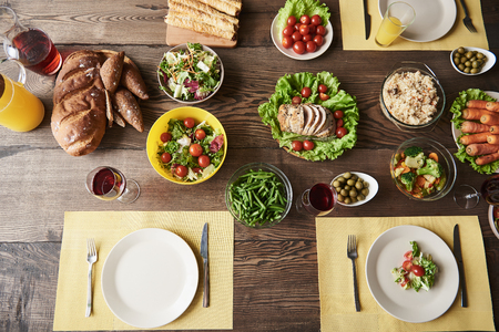 Top view of big brown table with white plates and bowls of healthy food. There are carrot, green asparagus, red tomatoes, lettuce, broccoli, olives, whole grain bread, baked meat and rice