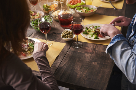 Close up man and woman sitting at table together. They are having salads on plates and drinking red wine. There are various wholesome dishes served in kitchen Stock Photo