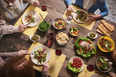 Top view of healthy food served for household members. They are sitting and eating together in kitchen vegetables, salads, meat and drinking wine