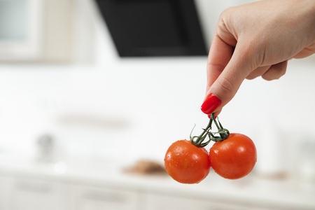Close up of female hand holding two red tomatoes. Kitchen is on background. Copy space