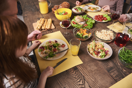 Close up of wooden table full of wholesome meal including salads, vegetables, meat and wine. Family members are sharing food together in kitchen at home