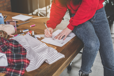 Close up female hands leading pencil while creating pattern of modern clothes Stock Photo