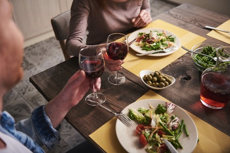 Dinner for two. Close up of couple hands clinking glasses. Female and male are sitting at table eating salads and vegetables and drinking red wine Stock Photo