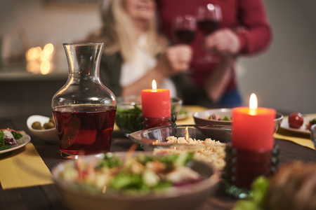 Focus of candles lit on festive dinner. There are red wine and variable dishes on table creating romantic atmosphere for couple on background