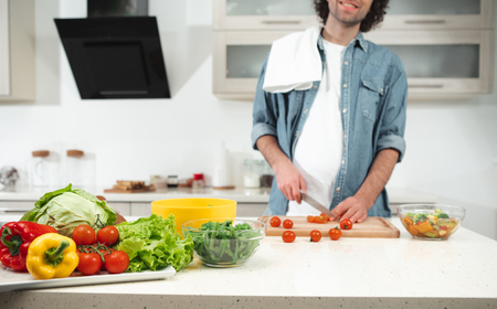 Cheerful young man is making cutting tomatoes while standing in kitchen. Focus on colorful vegetables om table