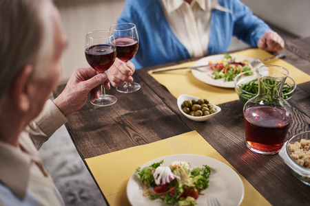 Close up of old woman and man hands cheering with red wine. They are eating salads and vegetables, enjoying dinner together