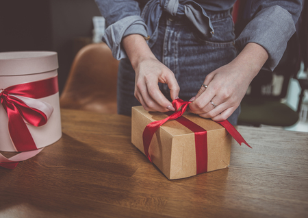 Close up woman arms tying beautiful red ribbon on gift wrap. She situating at desk during labor Stock Photo