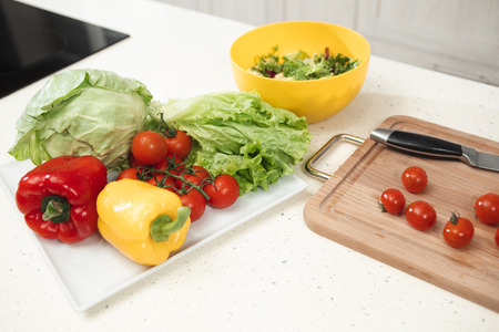 Close up of fresh vegetables on table. Tomatoes, peppers and cabbage with lettuce on tray near wooden board and knife