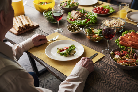 Close up of old man hands holding cutlery. He is sitting at table with carrots salad and bread, meat and rice on it. Lettuce with tomatoes lying on his white plate next to glass of red wine Stock Photo