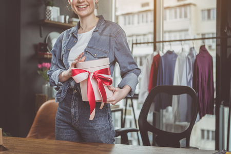 Outgoing lady holding beautiful present in hands while standing near table during job