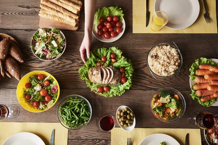 Top view of female hands taking plate with meat on dining table. There are various veggies including carrot, olives, asparagus, fresh tomatoes and salads. Drinks and bread lying nearby